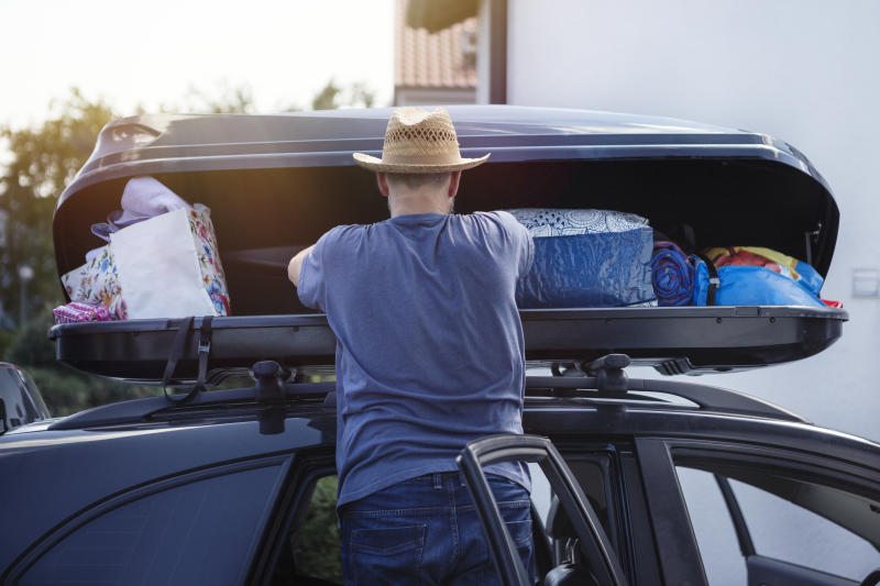 Man loading a car roof box with luggage before vacation