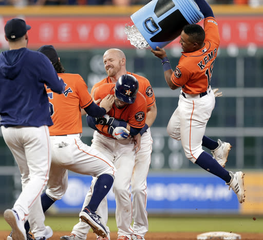Houston Astros' Tony Kemp, right, dumps water onto Robinson Chirinos, center as he is held by Derek Fisher, back, after Chirinos' double drove in the winning run against the Baltimore Orioles in the 11th inning of a baseball game Friday, June 7, 2019, in Houston. (AP Photo/Michael Wyke)