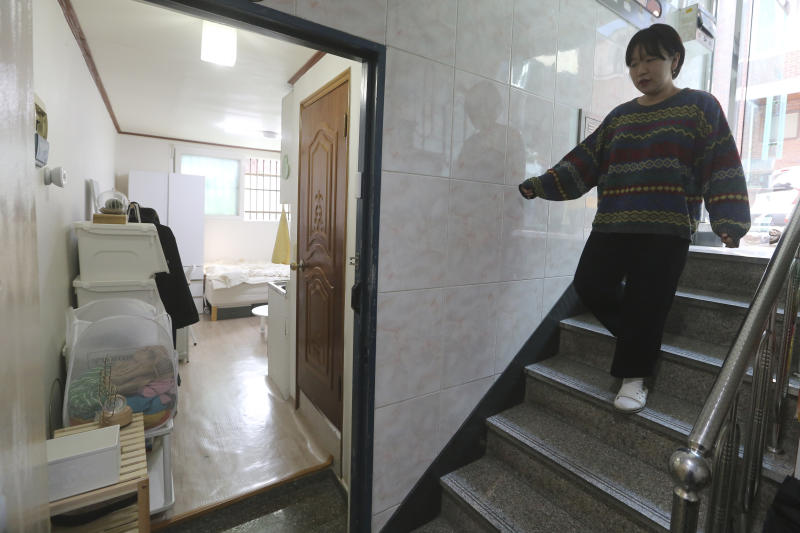 """Kim Da-hye, a 29-year-old South Korean, comes down the stairs to enter her semi-basement apartment in Seoul, South Korea, Saturday, Feb. 15, 2020. For many South Koreans, the image of a cramped basement apartment portrayed in the Oscar-winning film """"Parasite"""" rings true, bringing differences in their social status to worldwide attention. (AP Photo/Ahn Young-joon)"""