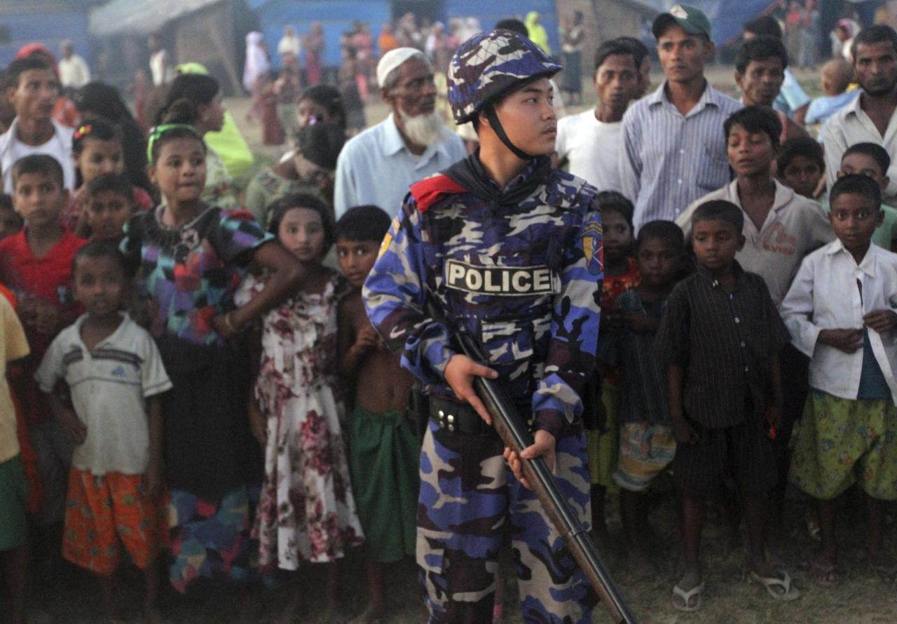 An armed police officer guards as Muslim refugees stand behind him at a refugee camp in Sittwe, capital of Rakhine State, western Myanmar, Saturday, Oct. 27, 2012. Western Myanmar appeared calm Saturday after almost a week of deadly ethnic strife, a government spokesman said as human rights groups called for action to end the violence that one said it has documented with satellite imagery. Rakhine state spokesman Win Myaing there were no immediate reports of fresh clashes between the Buddhist Rakhine and the Muslim Rohingya communities. (AP Photo/Khin Maung Win)