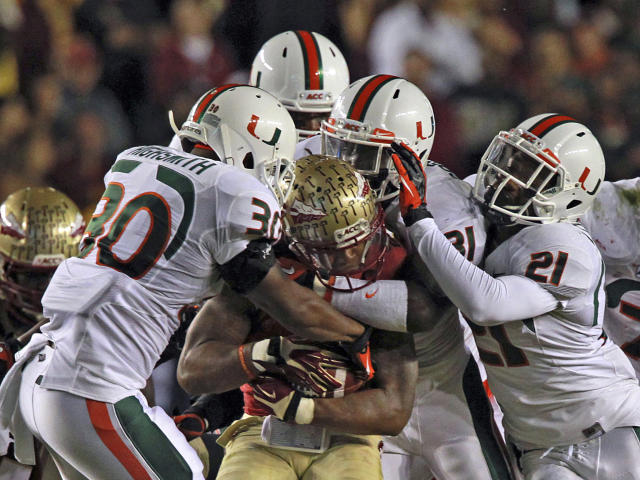 Miami's defense smoothers Florida State's Karlos Williams in the first quarter of an NCAA college football game Saturday, Nov. 2, 2013, in Tallahassee, Fla. (AP Photo/Miami Herald, Charles Trainor Jr.)