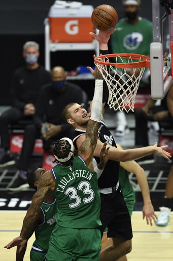 Los Angeles Clippers center Ivica Zubac, right, shoots over Dallas Mavericks center Willie Cauley-Stein during the second half of an NBA basketball game in Los Angeles Sunday, Dec. 27, 2020. (AP Photo/Kyusung Gong)