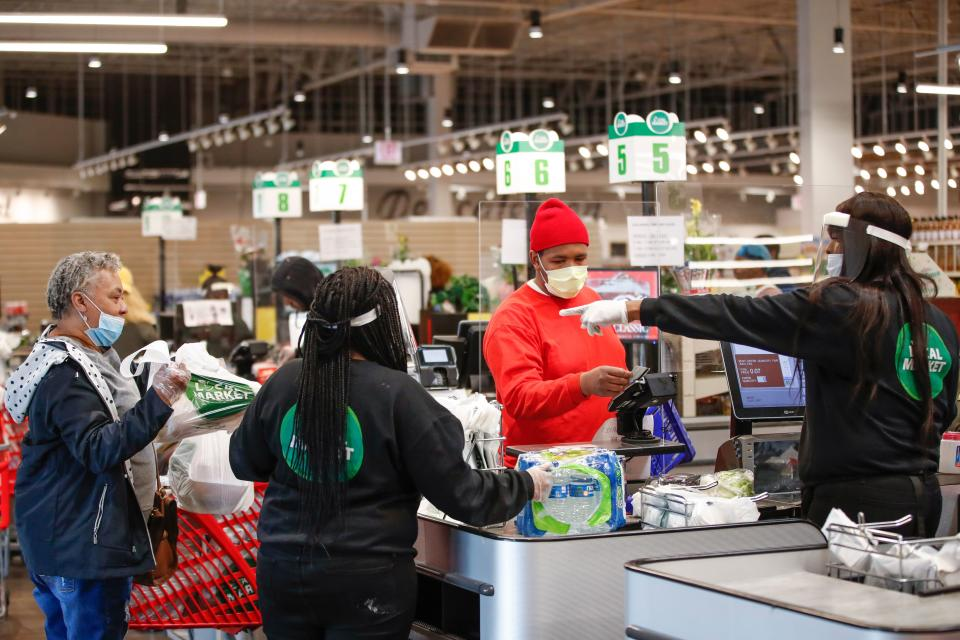 A customer pays for his groceries after shopping at the Local Market Foods store in Chicago, Illinois, on April 8, 2020. (Photo by KAMIL KRZACZYNSKI / AFP) (Photo by KAMIL KRZACZYNSKI/AFP via Getty Images)