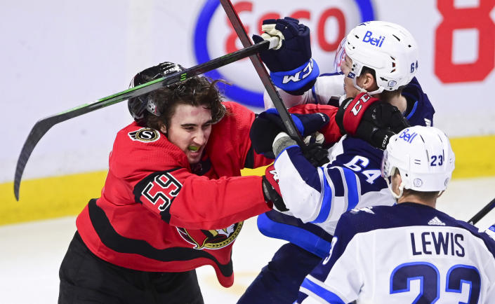 Ottawa Senators' Jack Kopacka (59) battles with Winnipeg Jets' Logan Stanley (64) during the second period of an NHL hockey game Wednesday, April 14, 2021, in Ottawa, Ontario. (Sean Kilpatrick/The Canadian Press via AP)