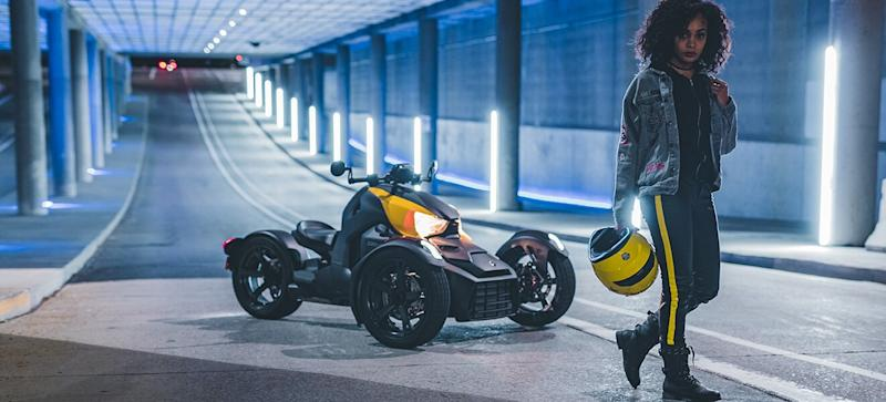 Woman standing next to three-wheeled motorcycle
