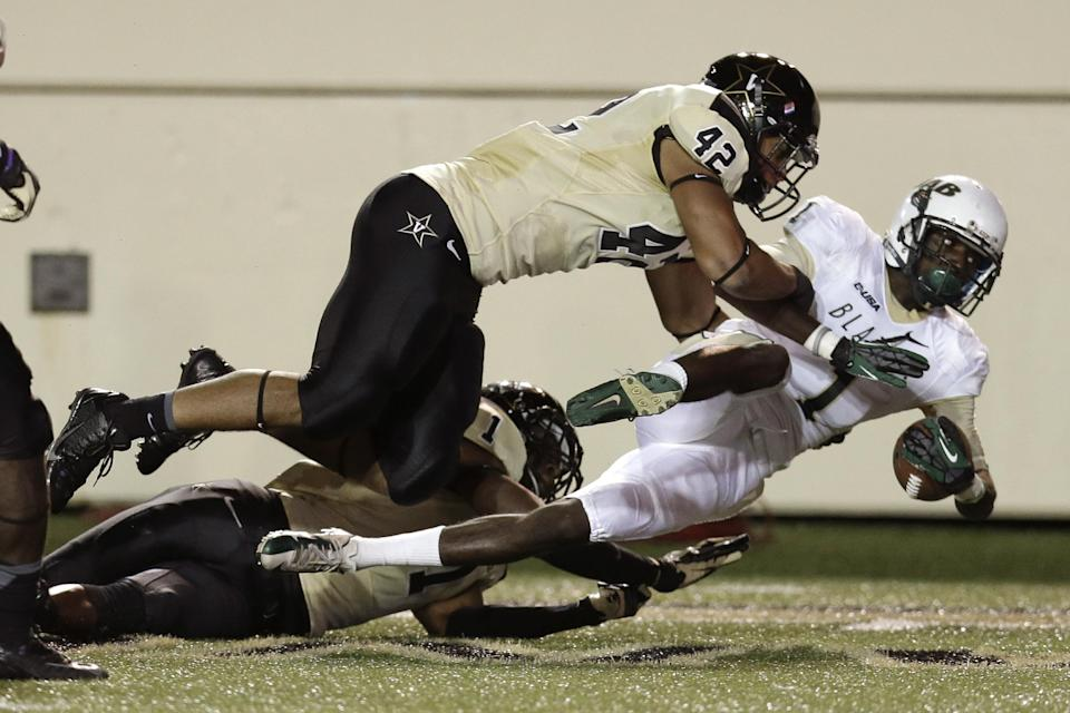 UAB wide receiver Jamarcus Nelson, right, is brought down by Vanderbilt defenders Kellen Williams (42) and Kenny Ladler (1) after a 38-yard gain in the second quarter of an NCAA college football game on Saturday, Sept. 28, 2013, in Nashville, Tenn. (AP Photo/Mark Humphrey)