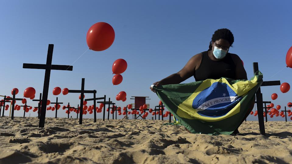 RIO DE JANEIRO, BRAZIL â AUGUST 09: A man holds Brazilian flag between red balloons replaced over and around crosses before they were released by people as a tribute to the 100,000 Brazilians lost their lives to coronavirus (Covid-19) pandemic at Copacabana beach in Rio de Janeiro, Brazil on August 09, 2020. The total number of registered deaths is 100,240, with 2,988,796 cases of the disease caused by the coronavirus. (Photo by Fabio Teixeira/Anadolu Agency via Getty Images)