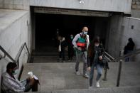 People wearing protective face masks exit a metro station, amid the coronavirus disease (COVID-19) pandemic, in Athens