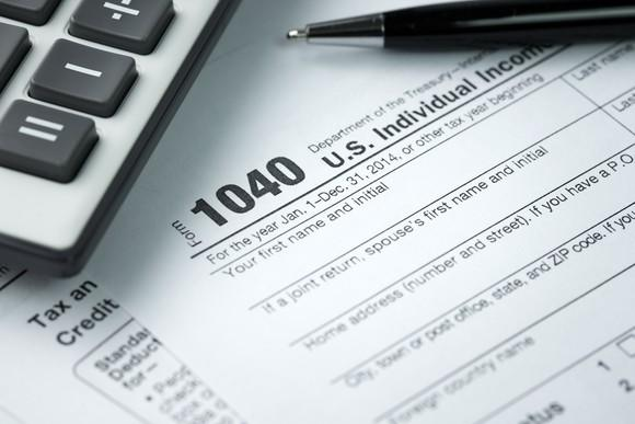 a 1040 tax form with calculator and pen in corner of picture.