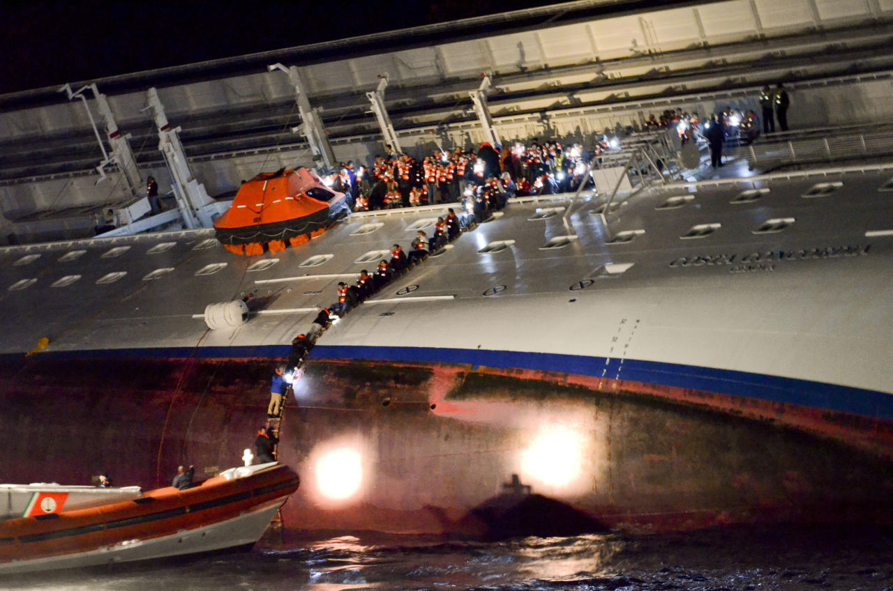 In this photo released by the Corriere Fiorentino newspaper Friday, March 2, 2012, and taken on Jan. 13, 2012, unidentified people abandon the Costa Concordia cruise ship laying on its starboard side after it ran aground off the coast of the Isola del Giglio island, Italy, gashing open the hull and forcing some 4,200 people aboard to evacuate aboard lifeboats to the nearby Isola del Giglio island. The first hearing to discuss evidence for the accident in which the Costa Concordia crashed, killing 32 people, will take place Saturday Feb. 3, 2012, in Grosseto, Italy. (AP Photo/Corriere Fiorentino) ITALY OUT