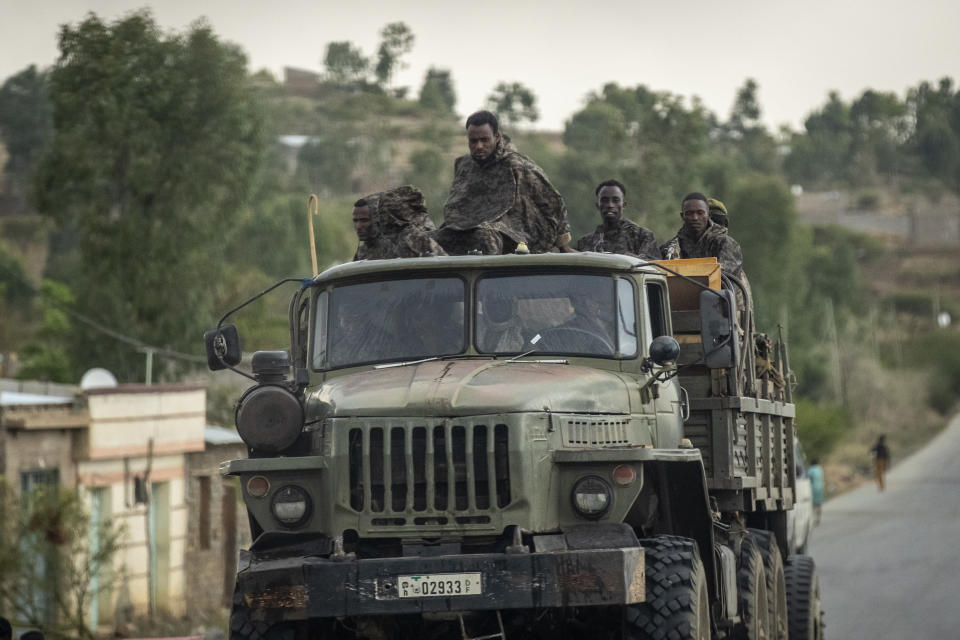 """FILE - In this Tuesday, May 11, 2021 file photo, Ethiopian government soldiers ride in the back of a truck on a road leading to Abi Adi, in the Tigray region of northern Ethiopia. In an interview with The Associated Press Tuesday, Sept 28, 2021, the United Nations humanitarian chief Martin Griffiths calls the crisis in Ethiopia a """"stain on our conscience"""" as children and others starve to death in the Tigray region under what the U.N. calls a de facto government blockade of food, medical supplies and fuel. (AP Photo/Ben Curtis, File)"""