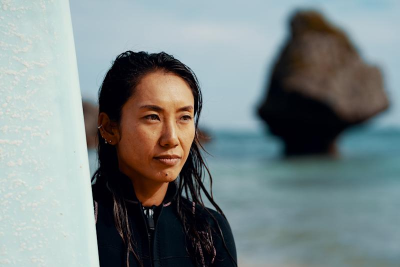 Portrait of a mature female athlete with her surfboard standing on a beach in Japan