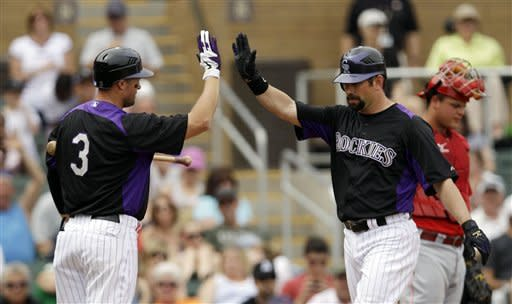 Colorado Rockies' Todd Helton, right, celebrates his solo home run with teammate Michael Cuddyer during the second inning of a spring training baseball game Cincinnati Reds on Sunday, March 25, 2012 in Scottsdale, Ariz. (AP Photo/Marcio Jose Sanchez)
