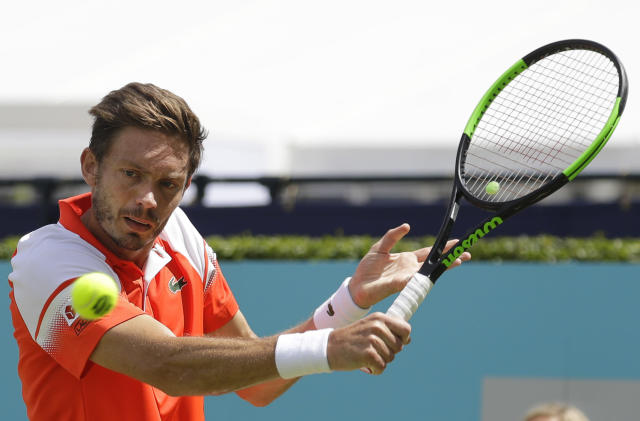 Nicolas Mahut of France plays a return to Gilles Simon of France during their quarterfinal singles match at the Queens Club tennis tournament in London, Friday, June 21, 2019. (AP Photo/Kirsty Wigglesworth)