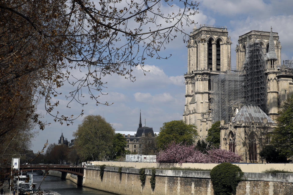 FILE - In this April 14, 2021 file photo, the Cathedral of Notre Dame is pictured on the eve of the second anniversary of its fire, in Paris. France's Notre Dame Cathedral is finally stable and secure enough for artisans to start rebuilding it, more than two years after the shocking fire that tore through its roof, knocked down its spire and threatened to bring the rest of the medieval monument down, too. (AP Photo/Christophe Ena, File)