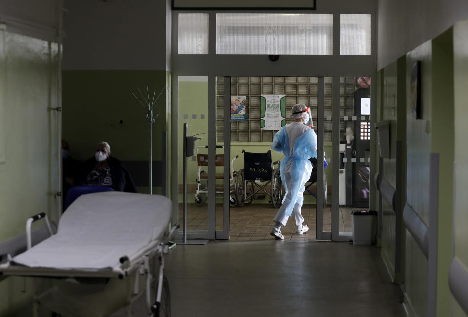 A health care worker walks in hallway at a hospital in Kyjov, Czech Republic, Thursday, Oct. 22, 2020. With cases surging in central Europe, some countries are calling in soldiers, firefighters, students and retired doctors to help shore up buckling health care systems. (AP Photo/Petr David Josek)