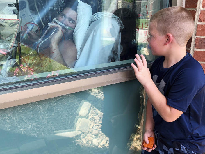 Six-year-old Brody Barker waves to his father, Daryl, from outside his hospital room July 26, 2021, in Osage Beach, Missouri, where Daryl has been hospitalized for nearly three weeks for COVID. Daryl told reporters he had resisted getting vaccinated. / Credit: Sarah Blake Morgan/AP