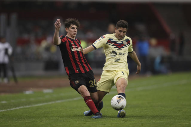 Santiago Caseres of America, right, challenges Emerson Hyndman of Atlanta United during a CONCACAF Champions League soccer game at Azteca stadium in Mexico City, Wednesday, March 11, 2020. (AP Photo/Fernando Llano)