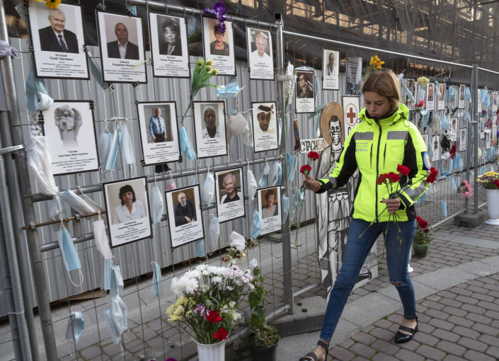 A woman puts flowers to portraits of St. Petersburg's medical workers who died from coronavirus infection during their work, hanging at an unofficial memorial in front of the local health department in St.Petersburg, Russia, Friday, Sept. 25, 2020. The number of daily new cases started to grow in late August in Russia, which has the fourth largest caseload in the world at 1.12 million infections. (AP Photo/Dmitri Lovetsky)