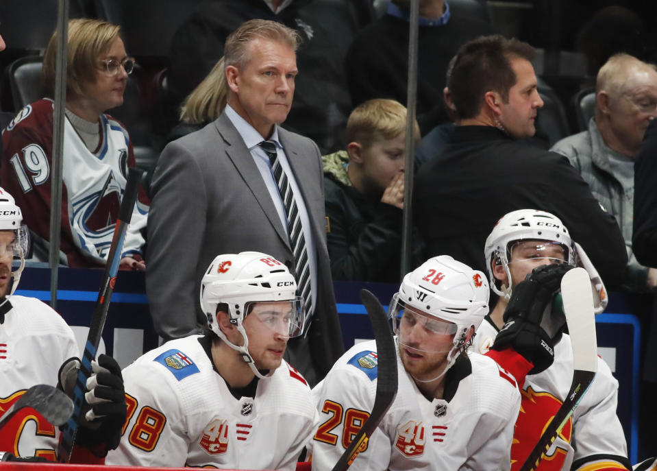 Calgary Flames interim head coach Geoff Ward looks on from the team box in the second period of an NHL hockey game against the Colorado Avalanche Monday, Dec. 9, 2019, in Denver. (AP Photo/David Zalubowski)