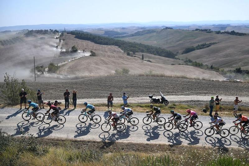 The pack of riders pedal through a dusty gravel road in the oneday classic cycling race Strade Bianche White Roads on August 1 2020 around Siena Tuscany Photo by Marco Bertorello AFP Photo by MARCO BERTORELLOAFP via Getty Images
