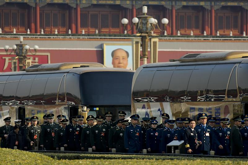 Delegates from China's People's Liberation Army (PLA) line-up as they arrive at the Great Hall of the People to attend a plenary session of the National People's Congress in Beijing, Saturday, March 4, 2017. China will raise its defense budget by about 7 percent this year, a government spokeswoman said Saturday, continuing a trend of lowered growth amid a slowing economy. (AP Photo/Andy Wong)