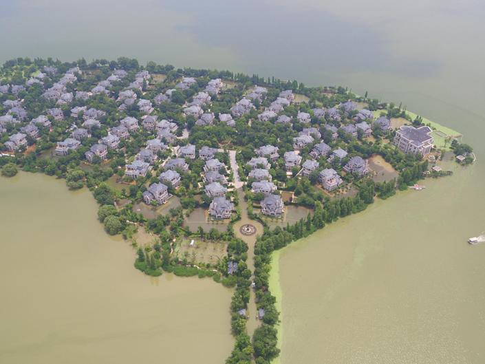 <p>An island holding one of the richest local neighborhoods is seen isolated by flood in Wuhan, Hubei province, July 8, 2016. (Photo: Stringer/REUTERS) </p>