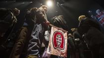 A young boy carries a team flag as mourners pay their respect to Montreal Canadiens legend Jean Beliveau during the public viewing for the Montreal Canadiens legend Jean Beliveau Sunday, Dec. 7, 2014, in Montreal. (AP Photo/The Canadian Press, Paul Chiasson)
