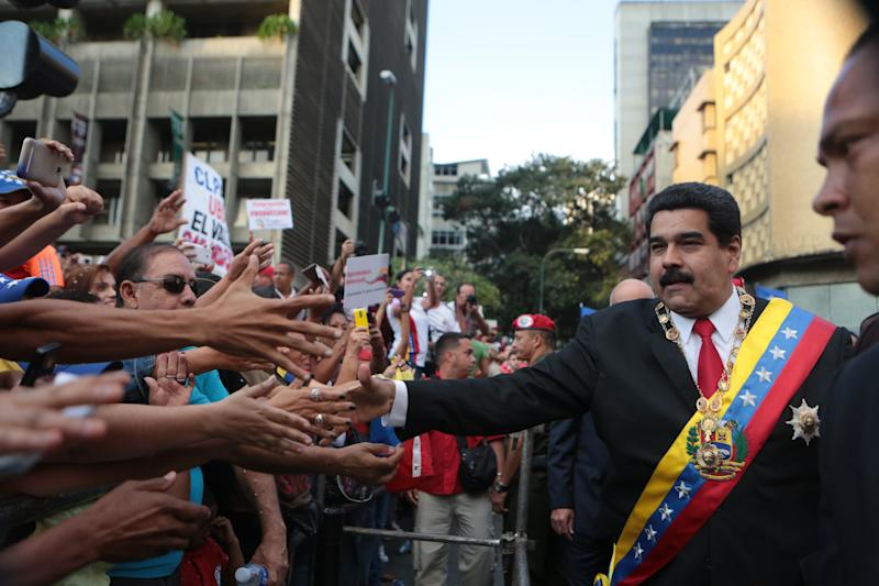 Venezuelan President Nicolas Maduro is greeted by supporters as he arrives at the parliament to deliver his annual message to the Nation in Caracas on January 21, 2015