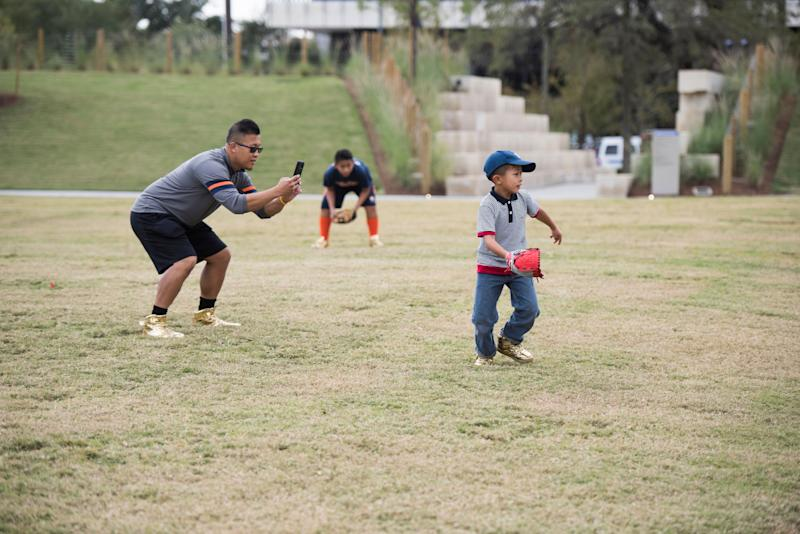 David Vuong and his sons Augustine-Pio, Alphonsus-Leo and Hyacinth-Michael play a game of baseball at Midtown Park in Houston.