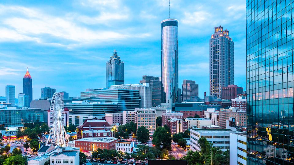 Skyline view of Downtown and Midtown Atlanta with ferris wheel from a rooftop bar and lounge.