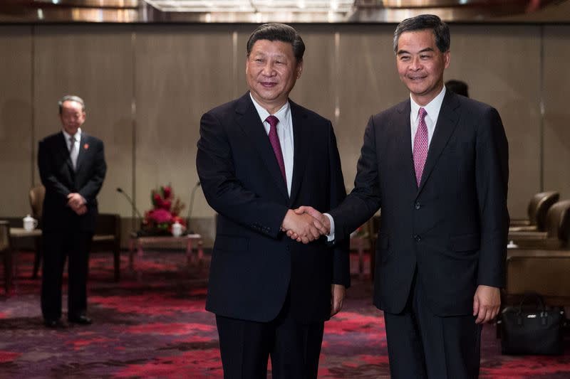 China's President Xi Jinping shakes hands with outgoing Hong Kong Chief Executive Leung Chun-ying during a meeting in a hotel in Hong Kong