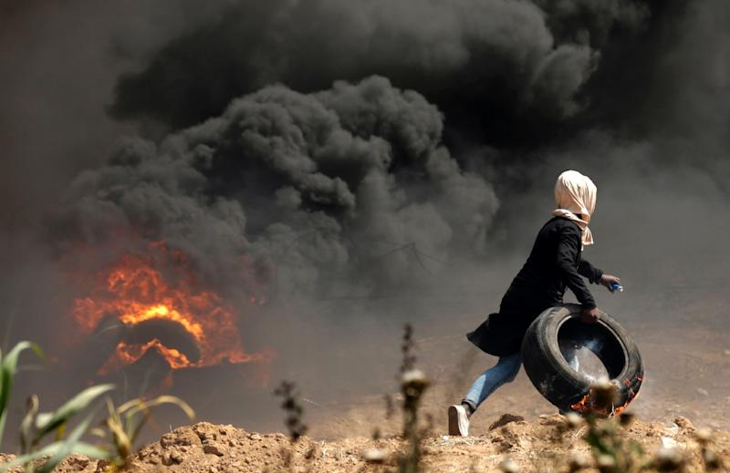 A Palestinian girl carries a burning tyre during clashes with Israeli security forces near the Gaza border on April 13, 2018 (AFP Photo/MAHMUD HAMS)