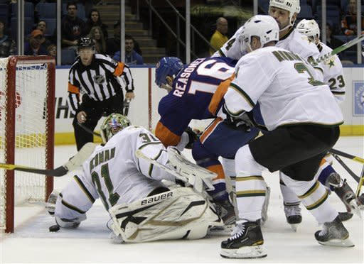 New York Islanders center Marty Reasoner (16) falls over Dallas Stars goalie Richard Bachman (31) as the puck slips between Bachman's legs for an Islanders goal in the second period of their NHL hockey game at Nassau Coliseum in Uniondale, N.Y., Thursday, Dec. 15, 2011. Islanders right wing Kyle Okposo (not shown) was credited with the goal. (AP Photo/Kathy Willens)