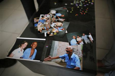 Pictures of Liu Guolian's father Liu Qian, who was a forced labourer by Mitsui Mining to work in their mines in Fukuoka of Japan, are seen on a table during an interview with Reuters on the outskirts of Beijing, April 28, 2014. REUTERS/Petar Kujundzic