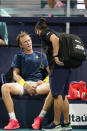 Sebastian Korda, left, is attended to by a trainer during a match against Andrey Rublev, of Russia, in the Miami Open tennis tournament, Thursday, April 1, 2021, in Miami Gardens, Fla. (AP Photo/Wilfredo Lee)