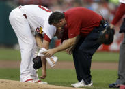 St. Louis Cardinals starting pitcher Shelby Miller, left, is checked on by trainer Chris Conroy after being struck by a ball hit by Los Angeles Dodgers' Carl Crawford during the first inning of a baseball game on Wednesday, Aug. 7, 2013, in St. Louis. The pitch was the second of the game an Miller was forced to leave the contest. (AP Photo/Jeff Roberson)