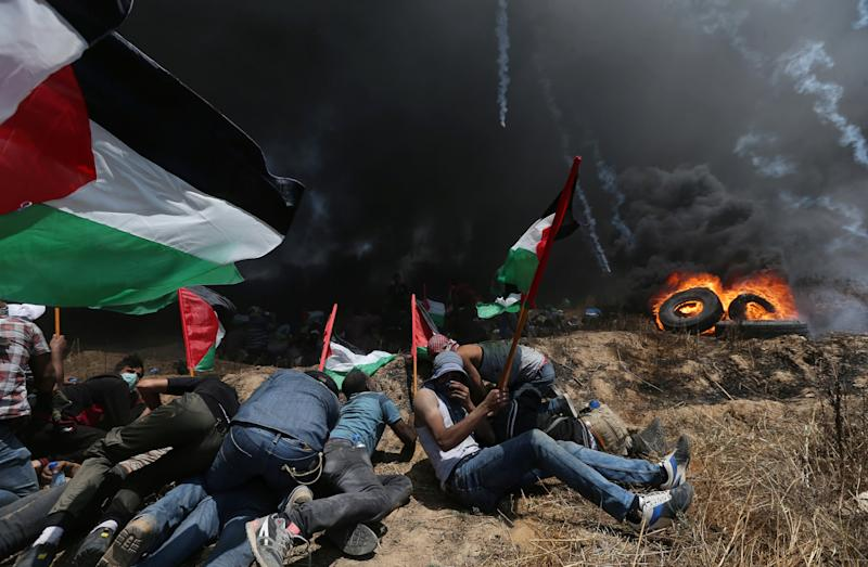 Palestinian demonstrators take cover from Israeli fire and tear gas during a protest against U.S. embassy move to Jerusalem. (Ibraheem Abu Mustafa / Reuters)