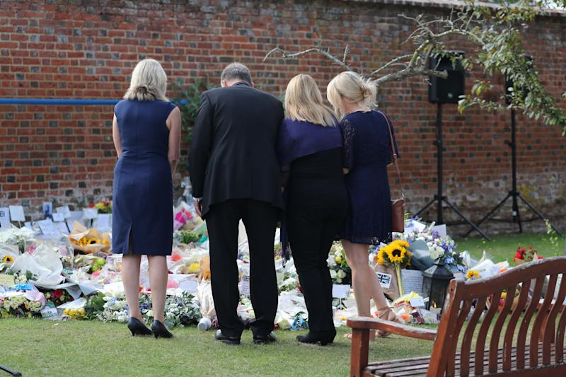 READING, ENGLAND - AUGUST 23: Family members look at floral tributes following a minute's silence for PC Andrew Harper at the Thames Valley Police Training Centre on August 23, 2019 in Sulhamstead near Reading, United Kingdom. PC Harper was killed on August 15 on the A4 near Reading and ongoing investigations have resulted in Jed Foster, 20, being accused of causing his death. Mr Foster has denied any involvement in PC Harper's death, but has yet to enter a plea at court. (Photo by Steve Parsons - WPA Pool/Getty Images)
