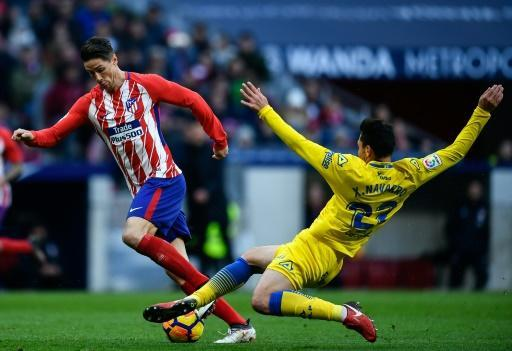 Atletico Madrid's forward Fernando Torres (L) is tackled by Las Palmas's defender Ximo Navarro during the Spanish league football match between Club Atletico de Madrid and UD Las Palmas