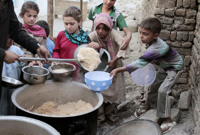 Afghan children receive free donated food by a private charity during the Muslim holy fasting month of Ramadan at a mosque in Kabul, Afghanistan on Thursday, Aug. 16, 2012. Ramadan is the ninth month of the Muslim year that lasts around 30 days, which strict fasting is observed from sunrise to sunset. (AP Photo/Musadeq Sadeq)