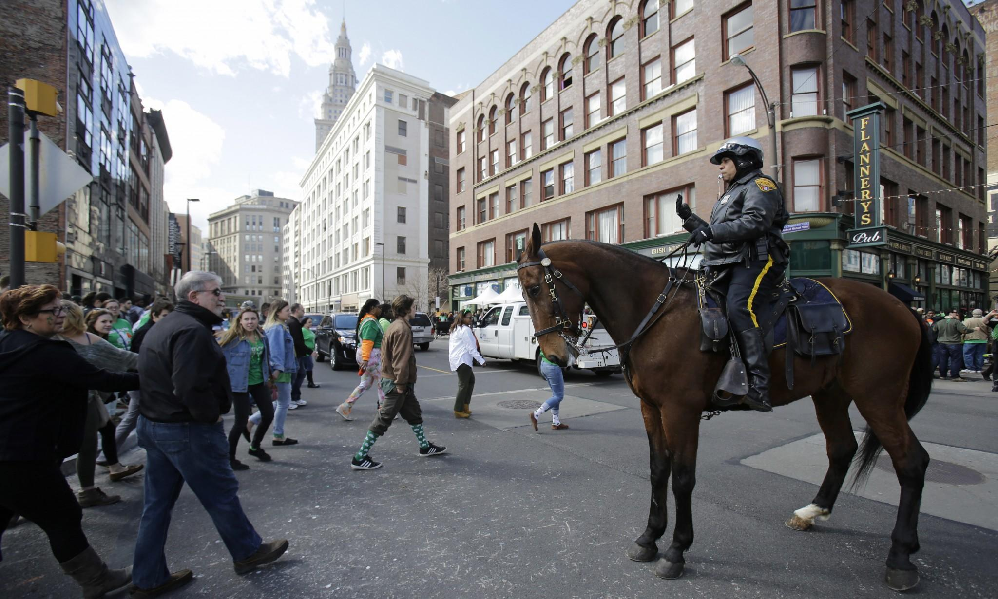 A Cleveland Police Mounted Unit patrolman directs pedestrians in downtown Cleveland on March 17, 2016. (Photo: Tony Dejak/AP)