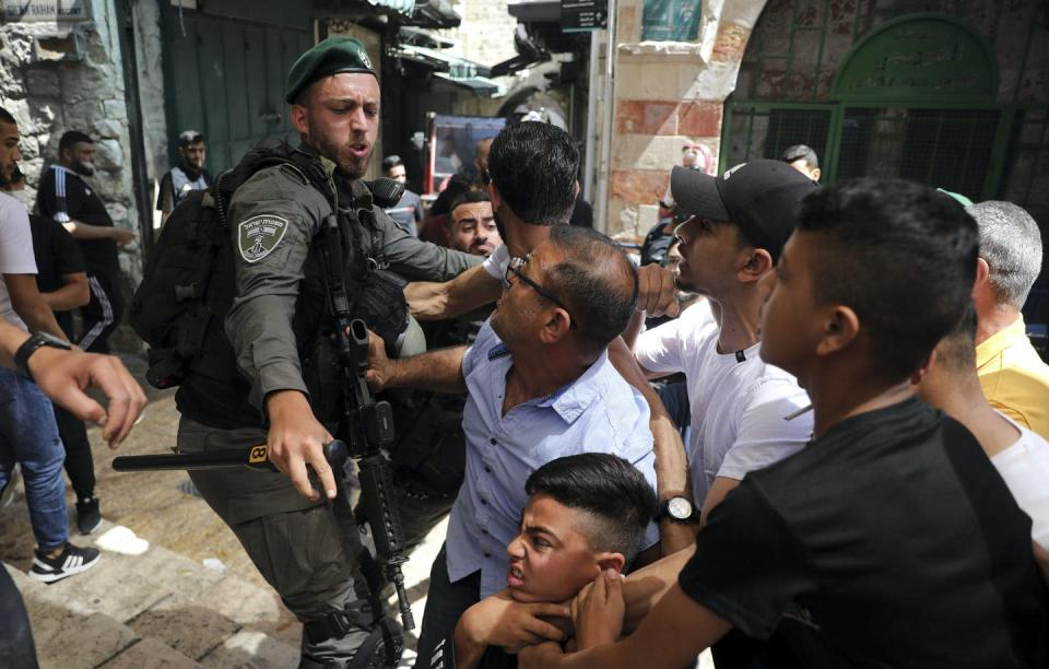 A police officer pushes away a crowd that includes a young child