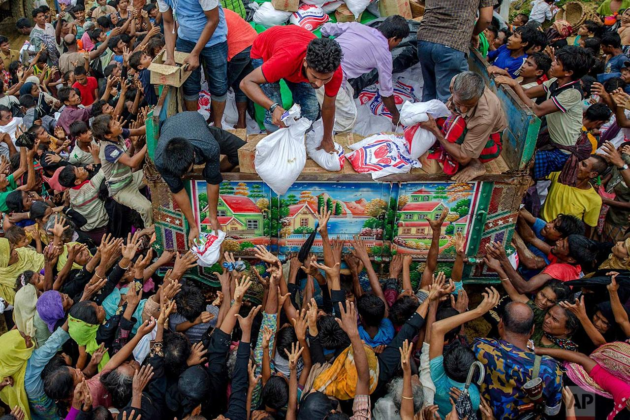 <p>Rohingya Muslims, who travelled from Myanmar into Bangladesh, stretch their arms out to collect food items distributed by aid agencies near Balukhali refugee camp, Bangladesh. (AP Photo/Dar Yasin) </p>