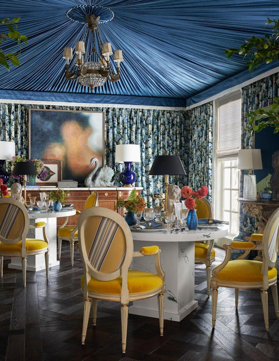 """<p>Talk about drama: In his """"Tent for New Beginnings"""" dining room, ELLE DECOR A-List designer <a href=""""https://coreydamenjenkins.com/"""" rel=""""nofollow noopener"""" target=""""_blank"""" data-ylk=""""slk:Corey Damen Jenkins"""" class=""""link rapid-noclick-resp"""">Corey Damen Jenkins</a> incorporated rich textures and exciting jewel tones to evoke the spectacle of a Cirque du Soleil performance. The tented ceiling is of a fabric hand-crafted by <a href=""""https://www.frenchfinish.com/"""" rel=""""nofollow noopener"""" target=""""_blank"""" data-ylk=""""slk:French Finish"""" class=""""link rapid-noclick-resp"""">French Finish</a>, while the wall's fabric is from the <a href=""""https://www.elledecor.com/design-decorate/a37594880/martyn-lawrence-bullard-the-shade-store/"""" rel=""""nofollow noopener"""" target=""""_blank"""" data-ylk=""""slk:Shade Store"""" class=""""link rapid-noclick-resp"""">Shade Store</a>. Antique Louis XVI chairs upholstered in bold yellow velvet surround quartz dining tables. The bold <a href=""""https://www.schotten-hansen.com/en/"""" rel=""""nofollow noopener"""" target=""""_blank"""" data-ylk=""""slk:Schotten & Hansen"""" class=""""link rapid-noclick-resp"""">Schotten & Hansen</a> parquet flooring was created in collaboration with Deven Gadula of <a href=""""https://www.first-last-always.com/company/home"""" rel=""""nofollow noopener"""" target=""""_blank"""" data-ylk=""""slk:First, Last & Always"""" class=""""link rapid-noclick-resp"""">First, Last & Always</a>.</p>"""