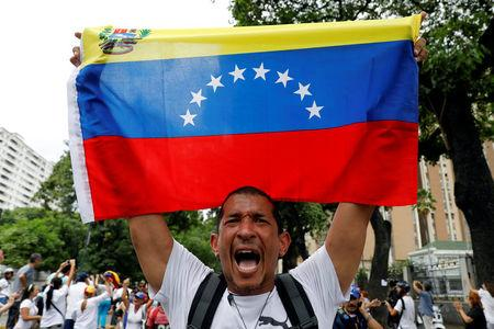 A demonstrator holds a Venezuelan flag as he takes part in a rally to honour victims of violence during a protest against Venezuela's President Nicolas Maduro's government in Caracas