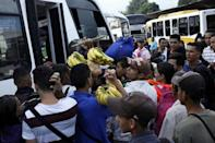People carrying goods try to find a spot on a bus to travel to the city of San Antonio near the Colombian border at the bus station in San Cristobal, Venezuela December 14, 2017. REUTERS/Carlos Eduardo Ramirez