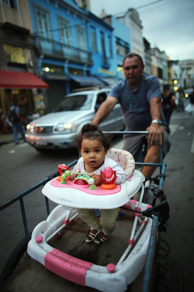 RIO DE JANEIRO, BRAZIL - NOVEMBER 01: A man is stopped at an intersection while bicycling with a child in a delivery cart in the port district as revitalization efforts continue on November 1, 2013 in Rio de Janeiro, Brazil. Ahead of the Rio 2016 Olympic Games, Rio has started a multibillion dollar urban renewal program of its port district that includes a double decker waterfront freeway being torn down to be replaced by tunnels, repaved roads, a tram network and other infrastructure improvements in the area. The 'Porto Maravilha' project is also expected to displace around 1,000 local residents. (Photo by Mario Tama/Getty Images)