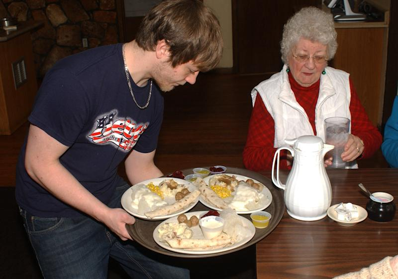 In this Dec. 20, 2012 photo, Ryan Bosma serves lutefisk to Marian Rasmussen at the VFW in Litchfield, Minn. Dozens of Minnesota Scandinavians and the people who love them still flock to the VFW Club in Litchfield every Thursday from November through January, where a $20 bill will get you a big steaming hunk of the frequently mocked fish dish known as lutefisk. (AP Photo/Ron Adams)