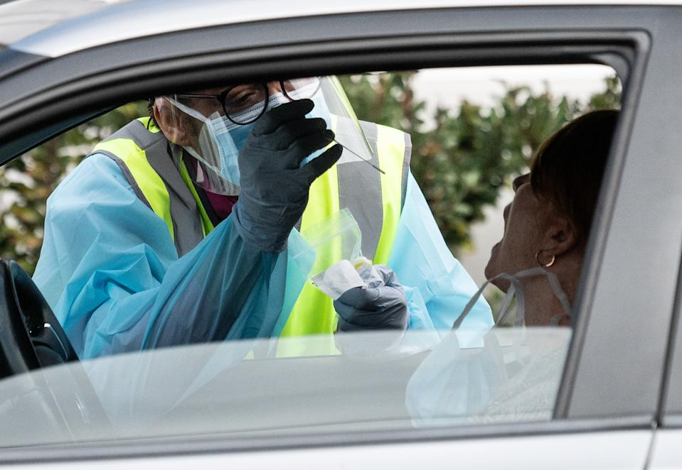 A NSW Health worker dressed in Personal Protective Equipment (PPE) testing a person for COVID-19 from their car.
